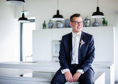 Hochzeitsfotos in Stuttgart Bräutigam lächelt in der Küche sitzend