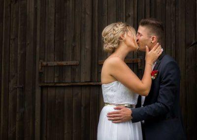 Hochzeitsfotos in Stuttgart Brautpaar küsst sich vor Scheune